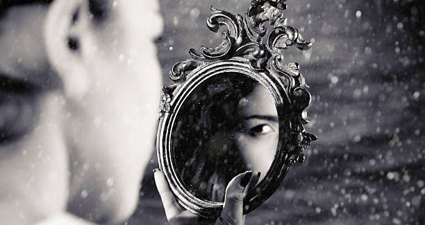 Girl watching mirror in her hand. Black and white